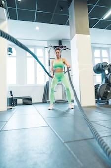 Mulher morena treinando com cordas no ginásio. ela está vestindo roupas esportivas verdes. ela está penteando o rabo de cavalo