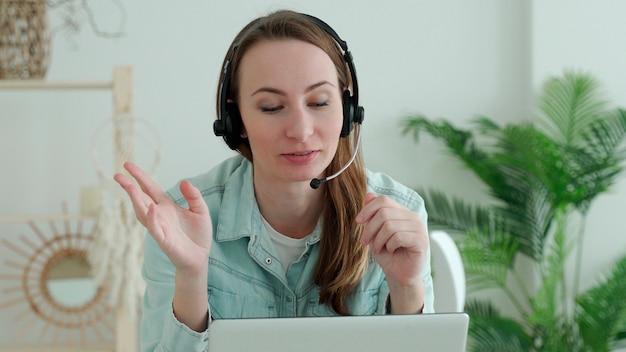Mulher morena usa fone de ouvido ligando no laptop fala com o professor on-line, estudando, trabalhando em casa.