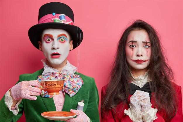 Mulher morena usa maquiagem de vampiro fantasma ou zumbi para o dia das bruxas, tem lábios ensanguentados e cicatrizes no rosto isoladas sobre a parede rosada do estúdio