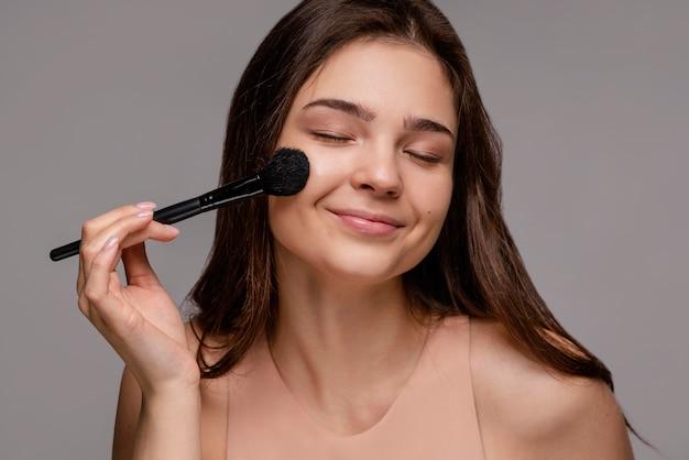 Mulher morena usando um pincel de maquiagem