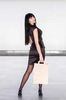 Mulher moreno de sorriso atrativa nova que guarda o saco de compras de papel, andando em uma alameda.