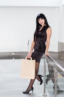 Mulher moreno de sorriso bonita nova que guarda o saco de compras de papel, andando em uma alameda.