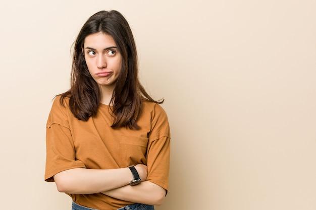 Mulher moreno nova contra uma parede bege infeliz com expressão sarcástica.