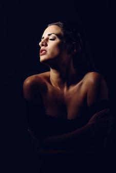 Mulher moreno nova na roupa interior preta na iluminação do claro-escuro.