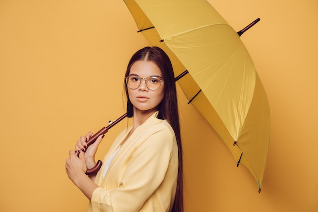 Mulher moreno nova nos vidros que vestem o revestimento amarelo que guarda o guarda-chuva amarelo sobre o fundo amarelo do estúdio.