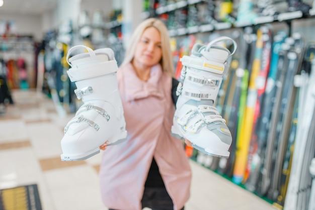 Mulher mostra botas brancas de esqui ou snowboard na loja de esportes.