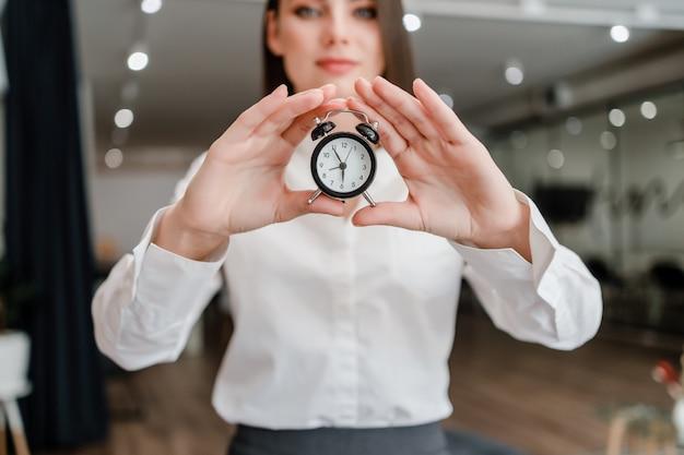 Mulher mostra despertador no escritório