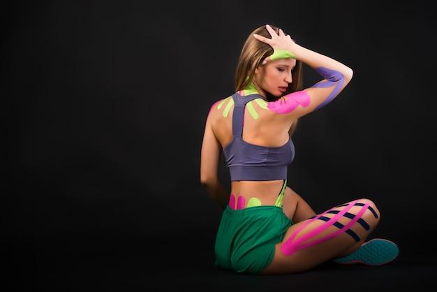 Mulher mostra fitas de kinesio coladas na barriga.
