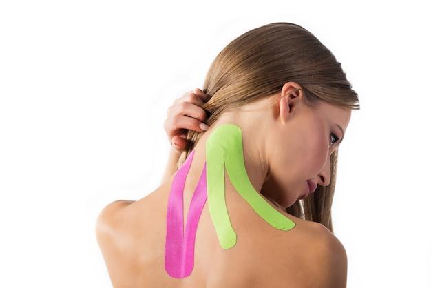 Mulher mostra fitas de kinesio coladas no pescoço, isoladas no fundo branco