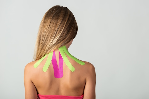 Mulher mostra fitas kinesio coladas ao pescoço.