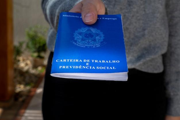 Mulher mostra o cartão de trabalho. carteira de trabalho brasileira