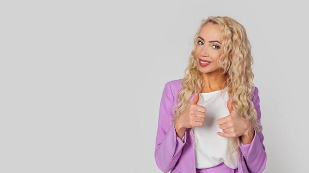 Mulher, mostra o polegar para cima e sorri amplamente, dá uma crítica positiva
