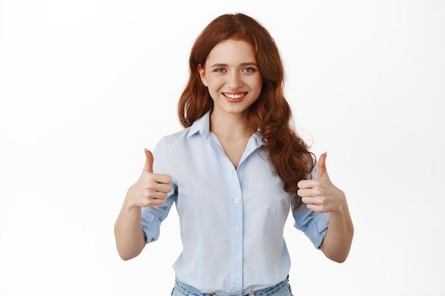 Mulher mostra os polegares em aprovação, sorrindo afirmativamente e diz que sim, elogiando o bom trabalho, elogiar, apoiar algo incrível, recomendar o produto