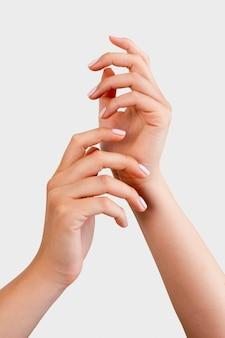 Mulher mostrando a manicure em fundo branco