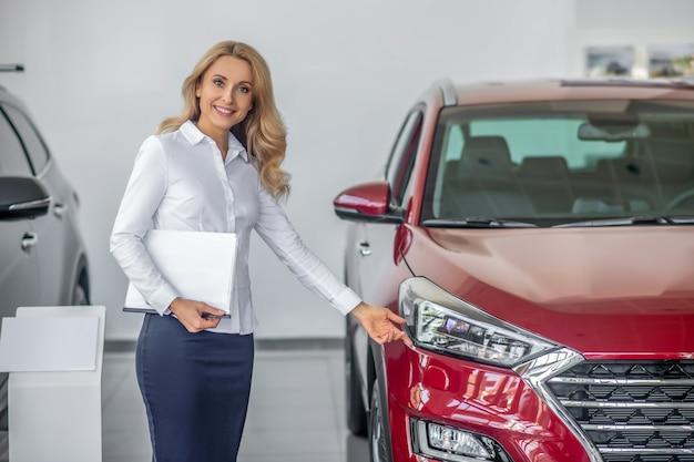 Mulher mostrando a mão tocante para o farol do carro