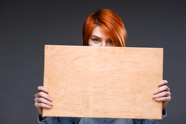 Mulher mostrando a placa de madeira na parede cinza