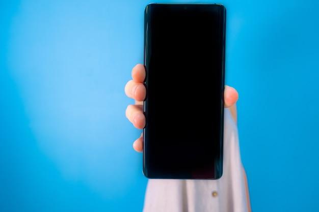 Mulher mostrando a tela do celular para a câmera sobre fundo azul com espaço de cópia.