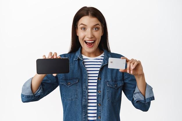 Mulher mostrando a tela do telefone móvel horizontal e cartão de crédito de desconto, sorrindo animado, recomendando a venda ou loja de compras online, em pé sobre o branco.