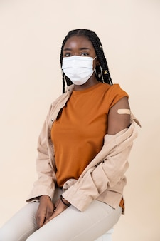 Mulher mostrando adesivo no braço após tomar vacina