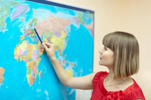 Mulher mostrando algo no mapa do mundo