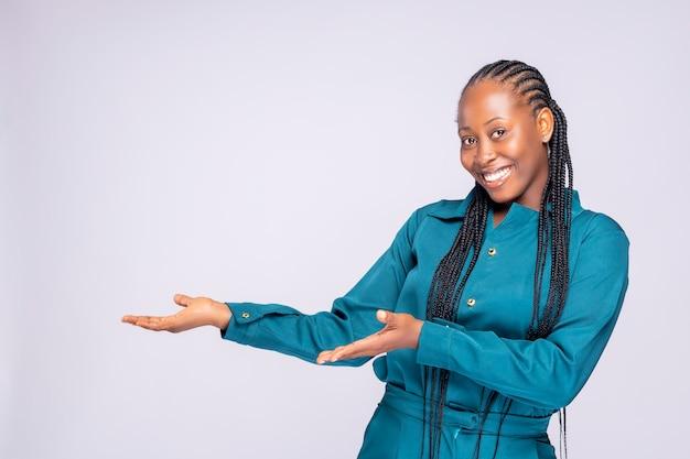 Mulher mostrando apontando no fundo. muito fresco e enérgico bela jovem negra da áfrica sorrindo feliz apresentando no fundo branco.