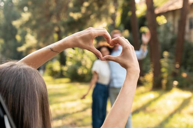 Mulher mostrando as mãos do coração para o casal ao ar livre