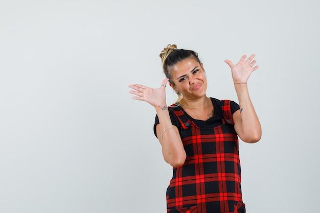 Mulher mostrando as palmas das mãos em um vestido avental e parecendo confiante, vista frontal.