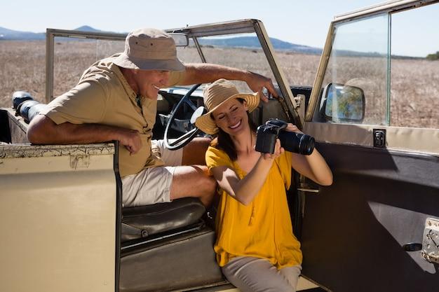 Mulher, mostrando, câmera, para, homem, em, veículo