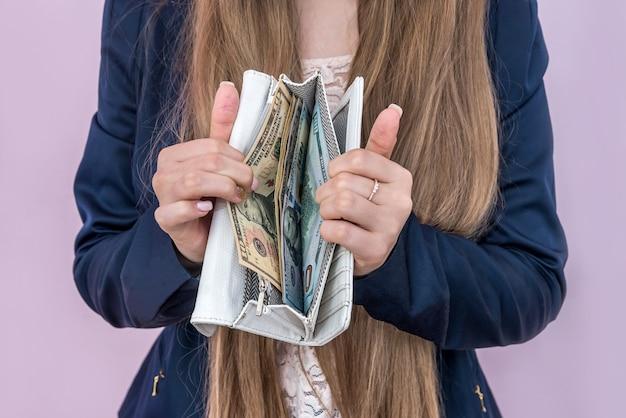 Mulher mostrando carteira com notas de dólar dentro