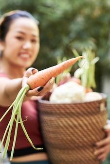 Mulher mostrando cenoura fresca