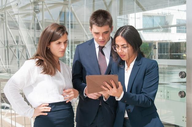 Mulher, mostrando, dados, ligado, tabuleta, colegas, olhar, concentrado
