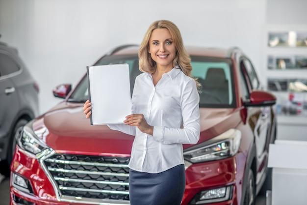 Mulher mostrando documento no showroom de carros