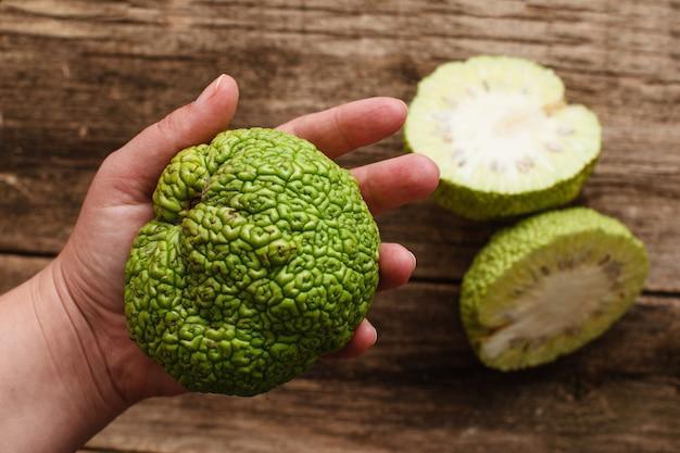 Mulher mostrando frutas tropicais verdes