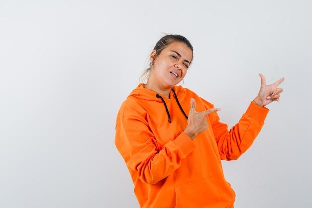 Mulher mostrando gesto de arma com um capuz laranja e parecendo confiante