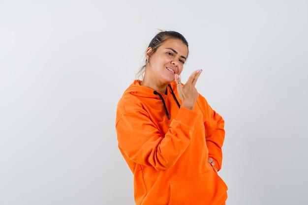 Mulher mostrando gesto de arma com um capuz laranja e parecendo feliz
