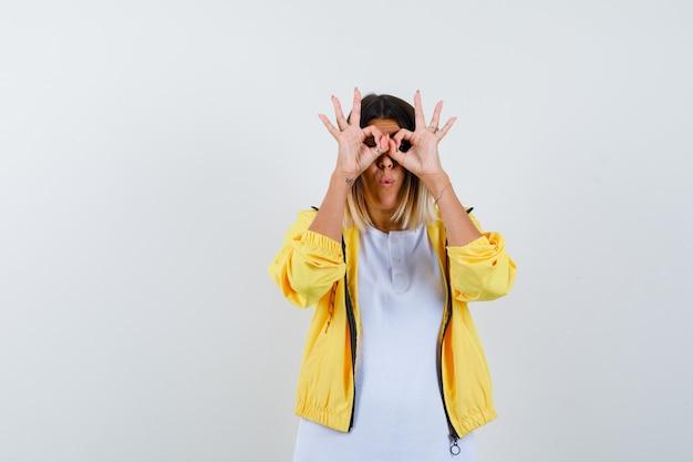 Mulher mostrando gesto de óculos em t-shirt, jaqueta e parecendo espantado. vista frontal.