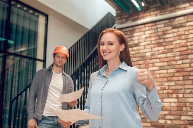 Mulher mostrando gesto de ok e funcionário atrás