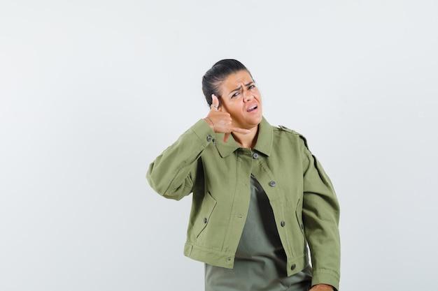 Mulher mostrando gesto de telefone com jaqueta, camiseta e parecendo confiante