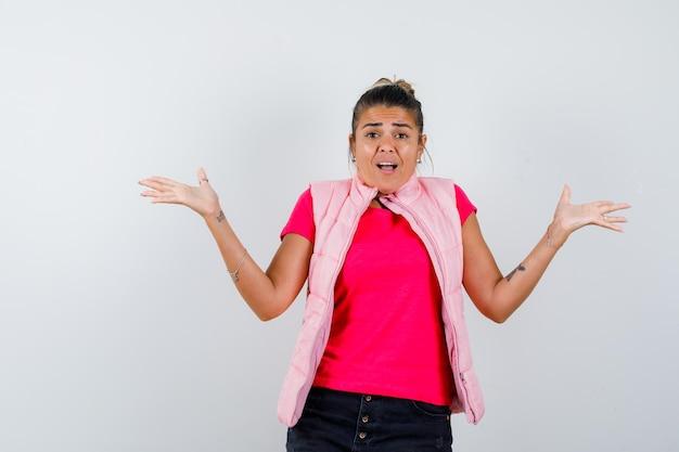 Mulher mostrando gesto desamparado em camiseta, colete e parecendo agitada