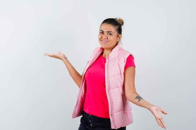 Mulher mostrando gesto desamparado em camiseta, colete e parecendo confusa