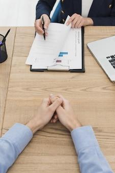 Mulher mostrando homem onde assinar contrato para novo emprego