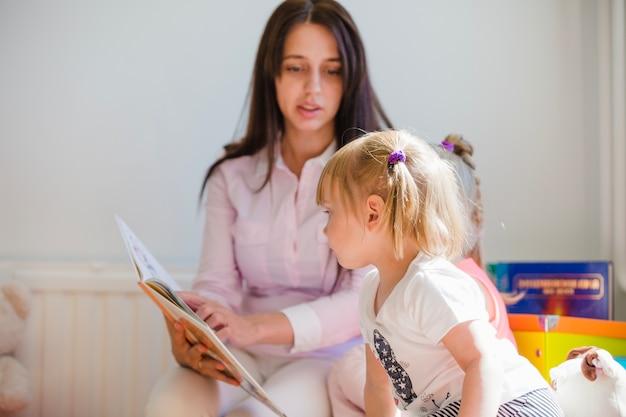 Mulher mostrando livro para menina