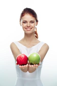 Mulher mostrando maçã verde e vermelha