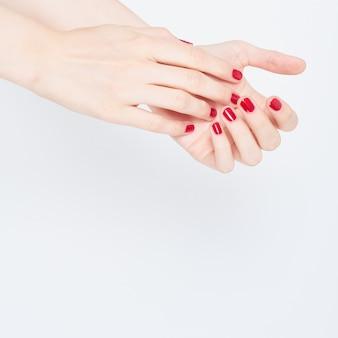 Mulher, mostrando, manicures, mãos, com, vermelho, esmalte branco, ligado