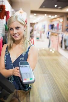 Mulher mostrando máquina de cartão de crédito