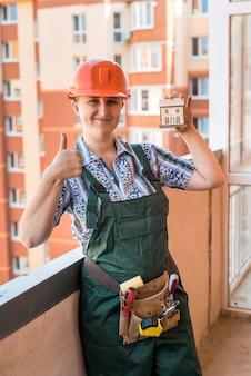 Mulher mostrando modelo de casa de madeira na varanda