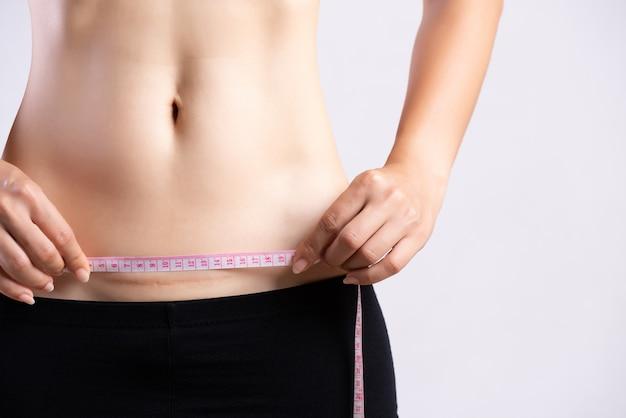 Mulher mostrando na cicatriz escura da barriga de uma cesariana com fita métrica