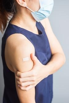 Mulher mostrando o braço com curativo após receber a vacina covid 19. vacinação, imunidade de rebanho, efeito colateral, eficiência da vacina e pandemia de coronavírus