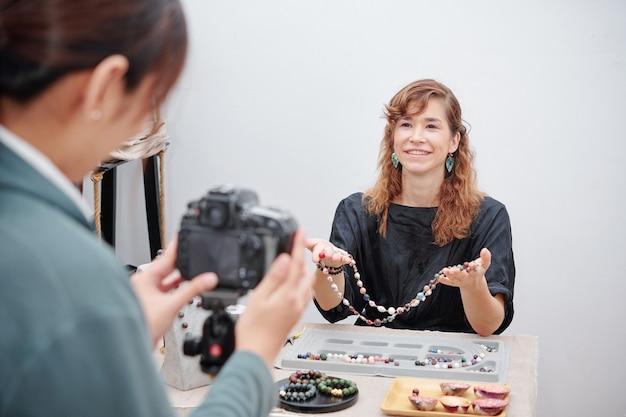 Mulher mostrando o colar que ela fez