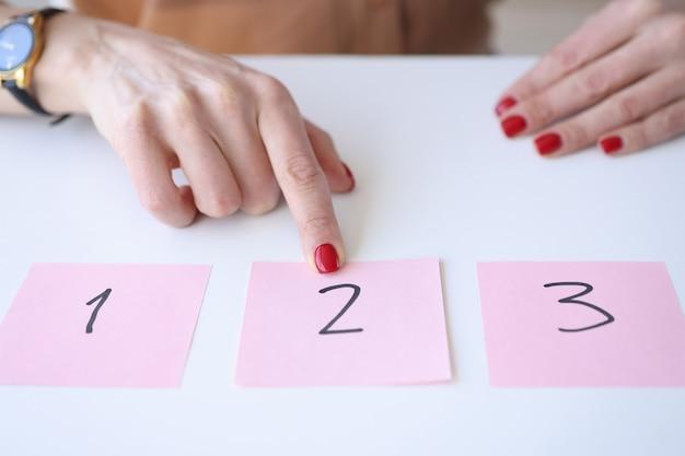 Mulher mostrando o dedo indicador para um adesivo com número
